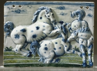 A Dutch faience high-relief plaquette, decorated in green, blue and white with three playful horses