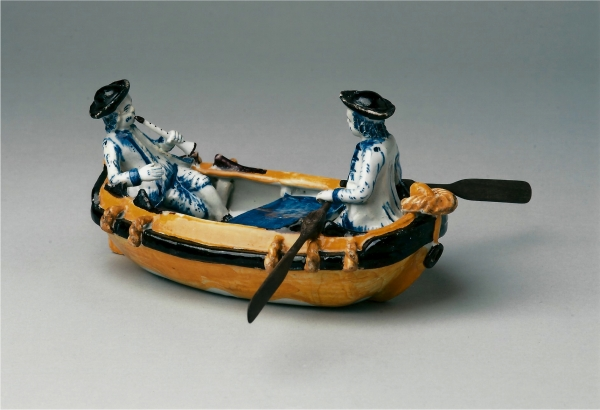 A Dutch Delft polychrome group, depicting two men in a rowing boat
