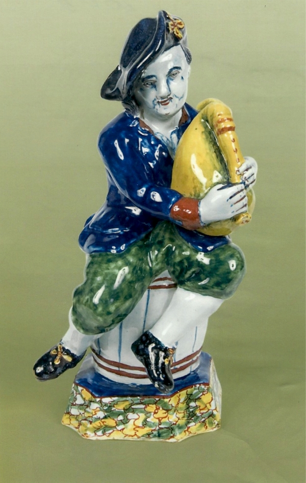 A Dutch Delft polychrome figure of a bagpipe-player seated on a barrel