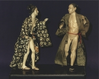 A pair of Japanese erotic figures of wrestlers each waering a kimono, made of pipe-clay
