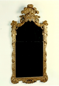 A mirror in a Dutch carved and gilded limewood frame, after a design of Daniel Marot