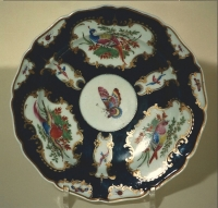 A Worchester plate, painted with bright colours on a dark blue ground