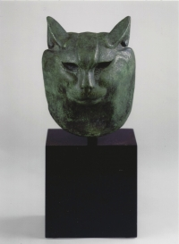 A green patinated sculpture, head of a tomcat