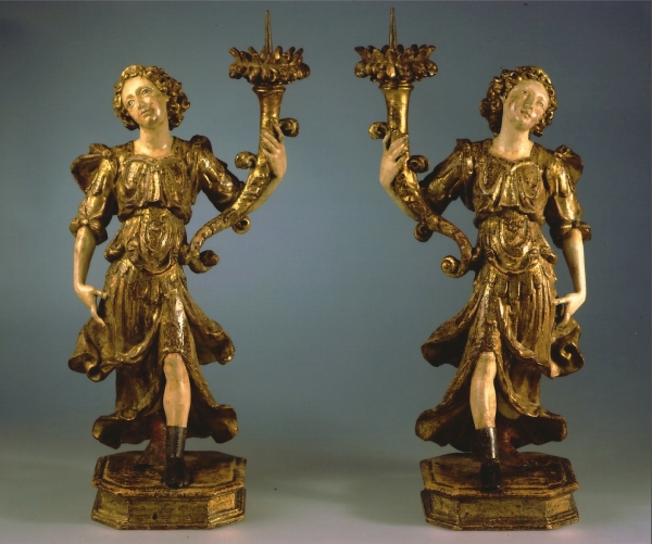 A pair of polychrome and gilded limewood candle-bearing angels