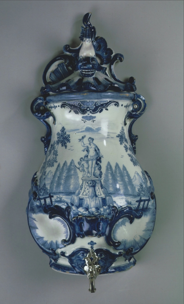 A Dutch wall fountain, blue and white faience with the original silver tap